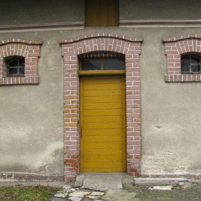 Ceglane obramowania okien idrzwi zabudowań gospodarczych zwidocznym powyżej gzymsem